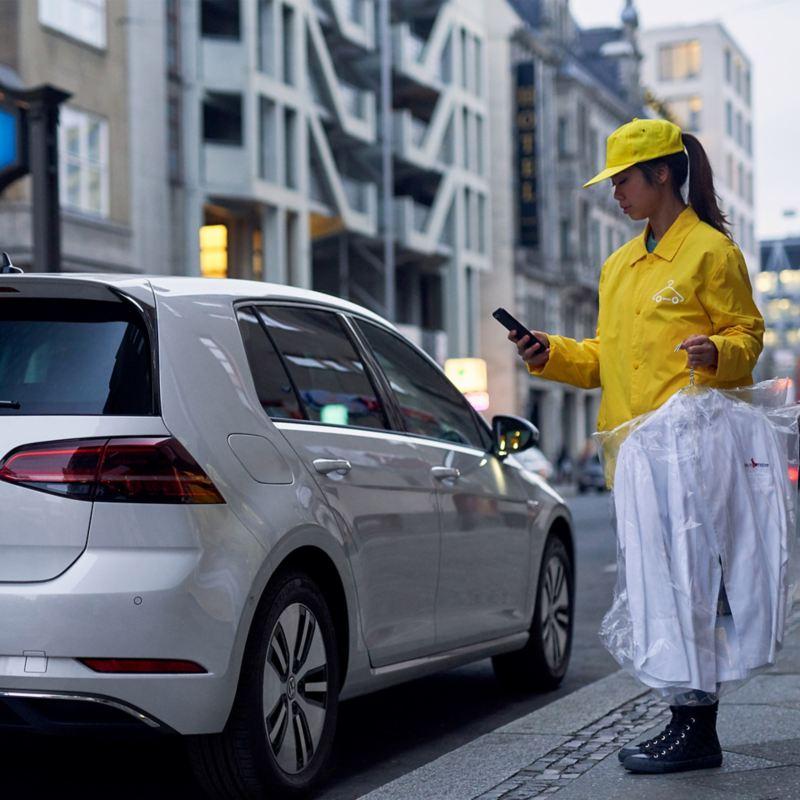 WeDeliver Service-Person mit Smartphone und gewaschenen Hemden an einem parkenden VW e-Golf