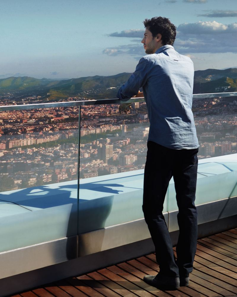 A man is standing on a roof terrace on a hill, looking out over the skyline of a coastal town.