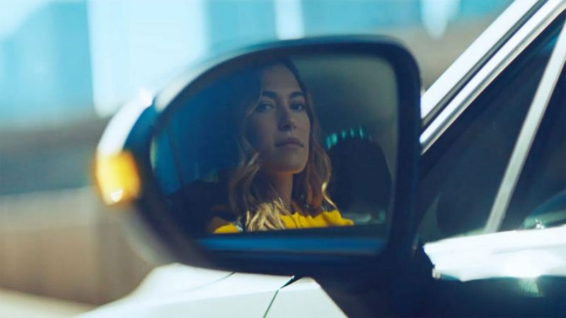 A woman reflects herself in the side mirror of a Volkswagen