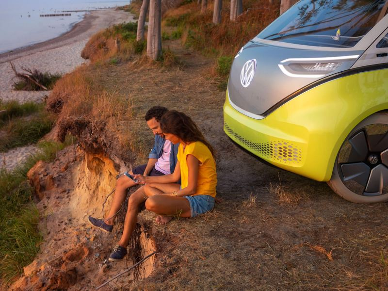 The Volkswagen ID. Buzz, parked on a beach cliff, owners sat in front.