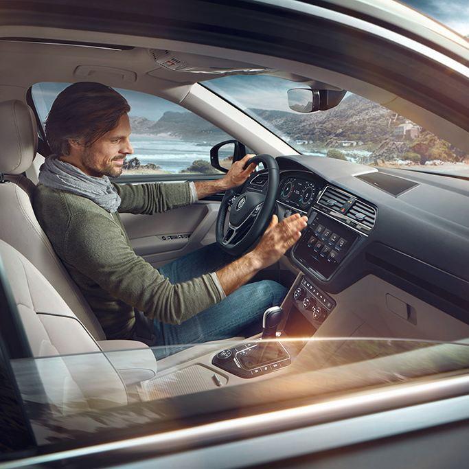 Uomo alla guida di una Volkswagen Tiguan Allspace.