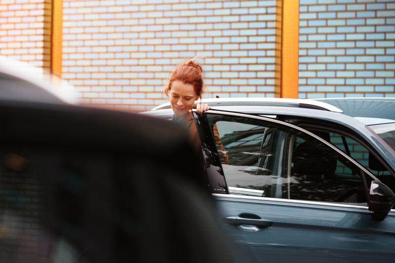 Kvinna vid öppen bildörr