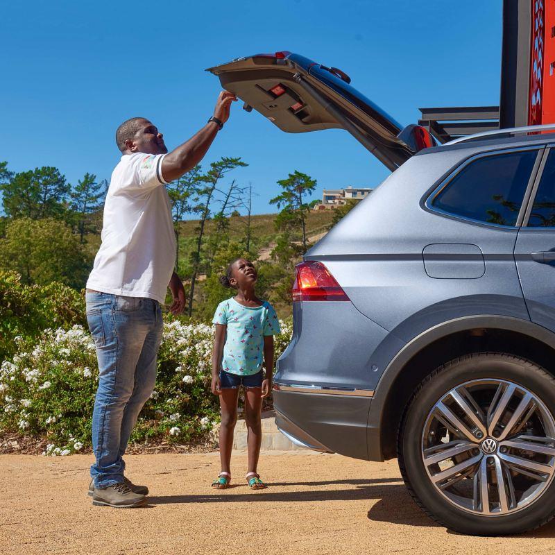 Vorarbeiter Thulani inspiziert mit seiner Tochter den Kofferraum des Tiguan Allspace