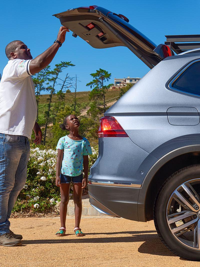Thulani und Tochter beladen den Kofferraum des VW Tiguan Allspace