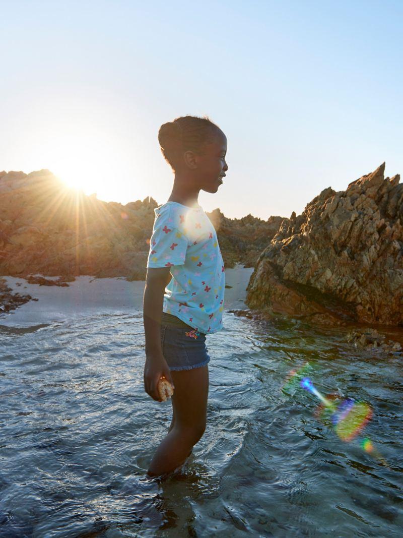 Tochter Charlotte planscht bei Abendlicht im Meer