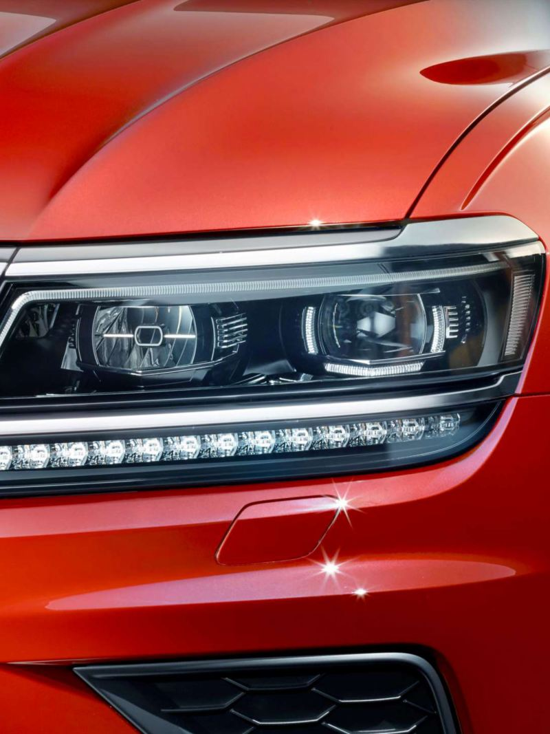 A closeup of a red Volkswagen Tiguan featuring the LED head light cluster