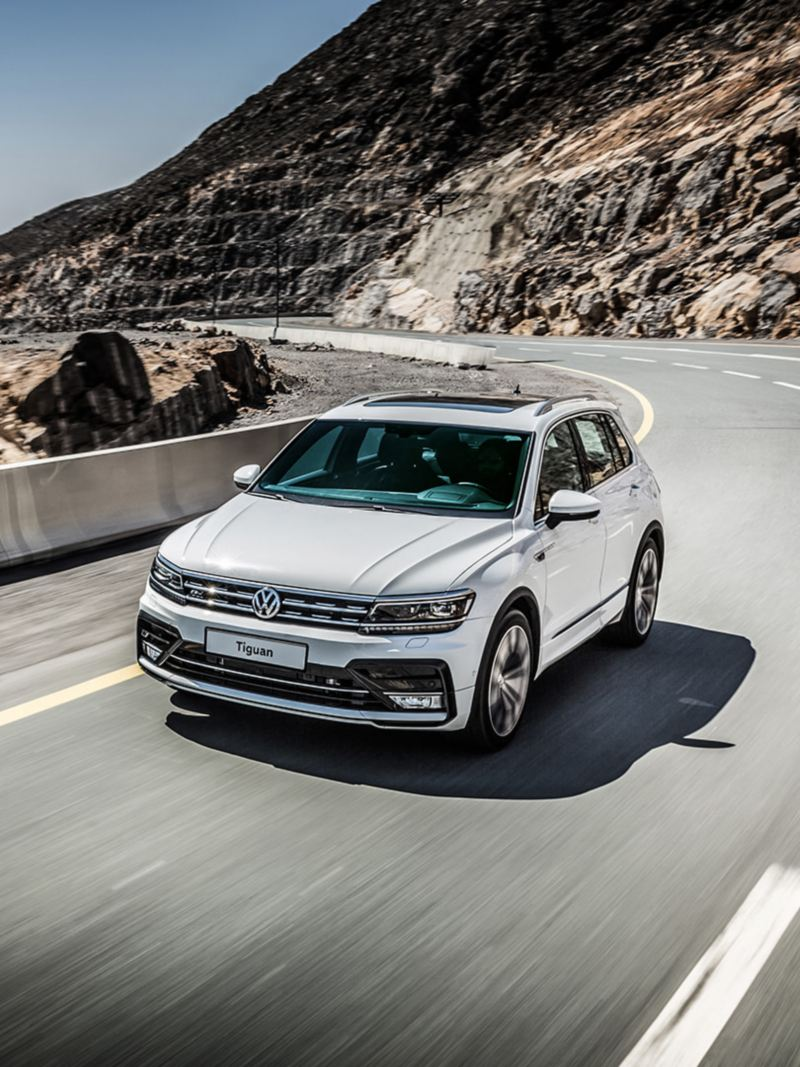A white Volkswagen Tiguan driving around a mountain bend