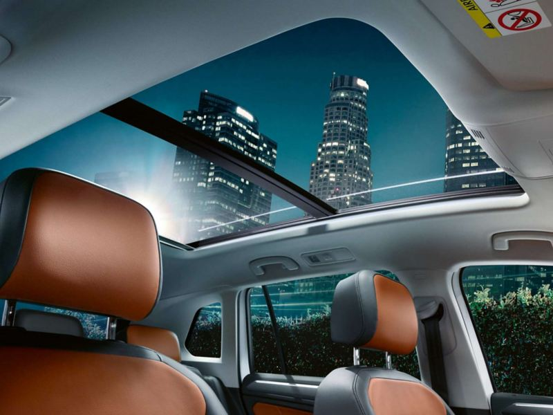 The Volkswagen Tiguan's interior with a view of the panoramic sunroof and orange seats
