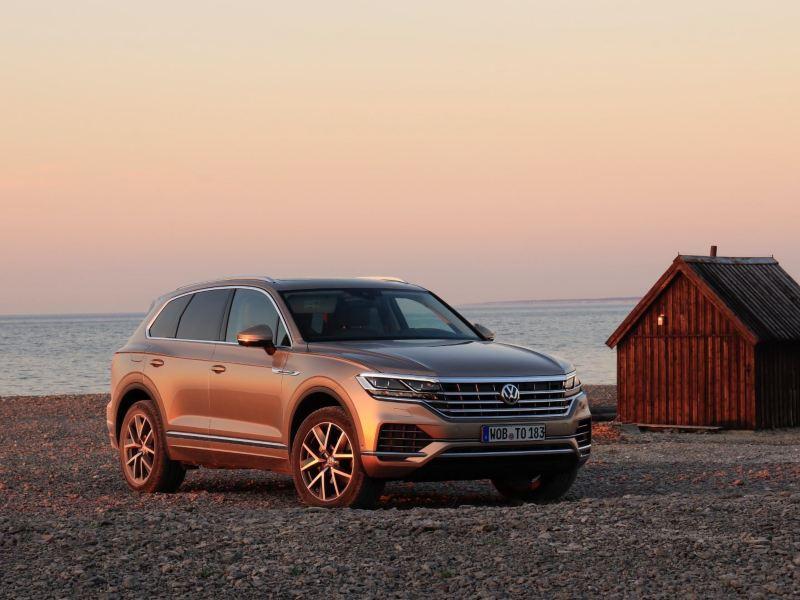 VW Touareg på stenstrand med havet i bakgrunden