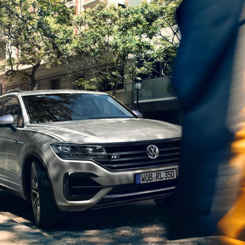 Man and woman walking in front of blue Touareg