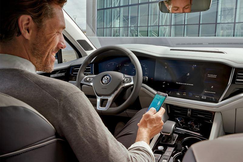 uomo collega smartphone al navigatore dell'auto