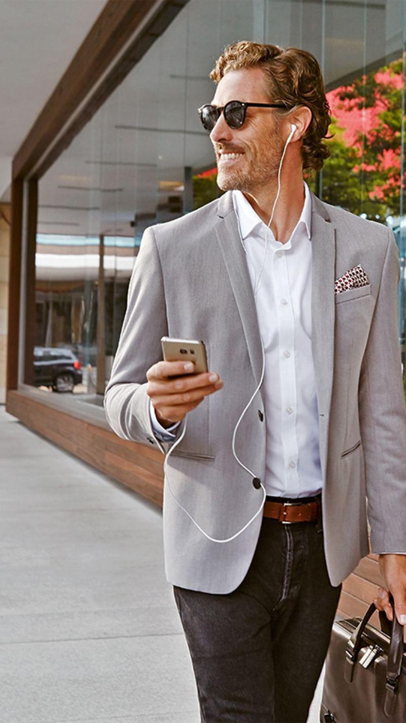 Un uomo che cammina col cellulare in mano - Contatti Volkswagen