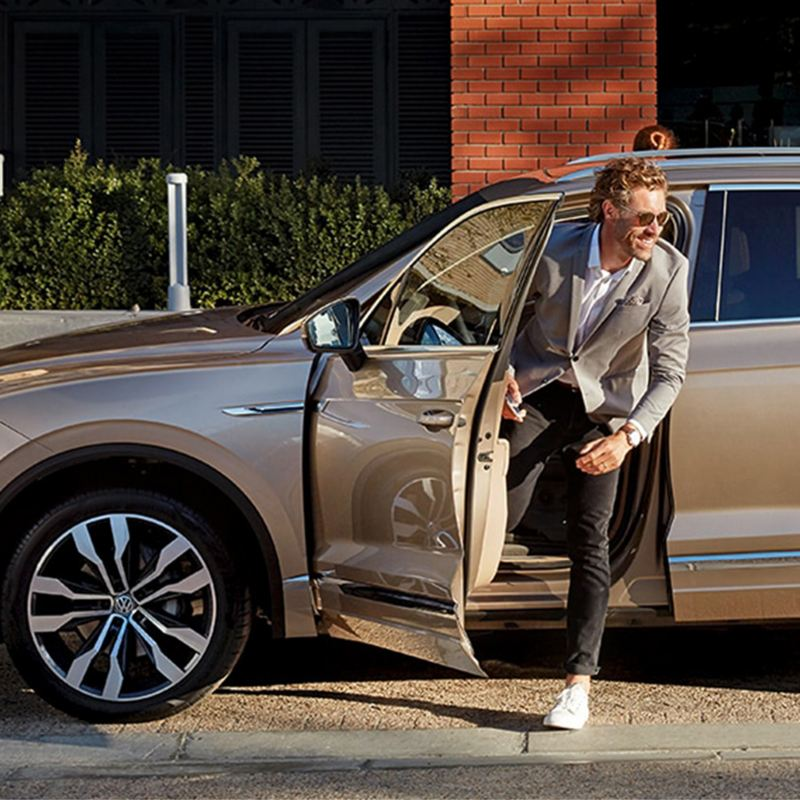 Un uomo scende dalla sua auto Volkswagen Business noleggiata