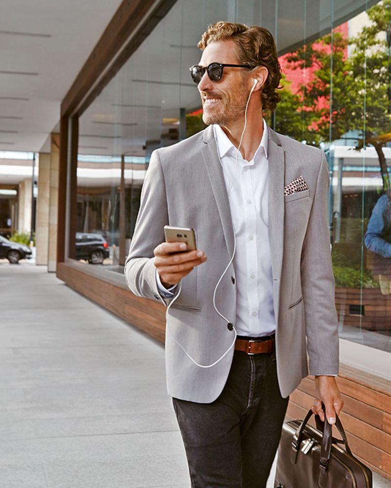 Man walking down the street holding phone