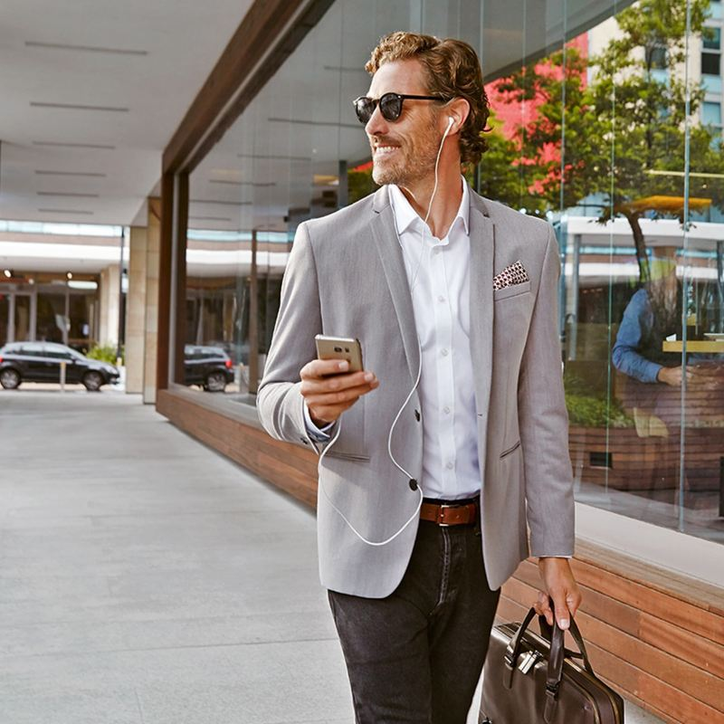 A business man walking down the street on his phone