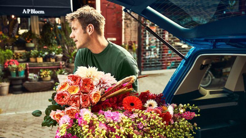 Alexander Posthuma steht mit einem großen Bouquet am geöffneten Kofferraum des Touran
