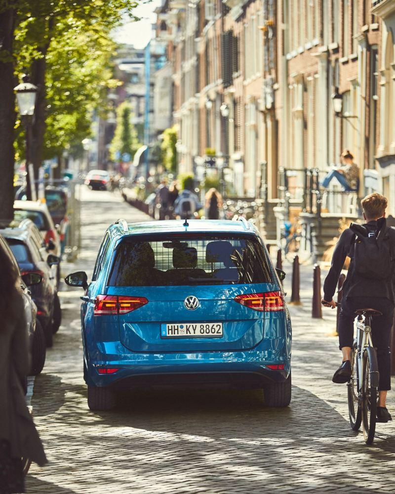 Heckansicht auf einen blauen VW Touran, der durch eine enge Straße in der Stadt fährt. Neben ihm ein Fahrradfahrer.