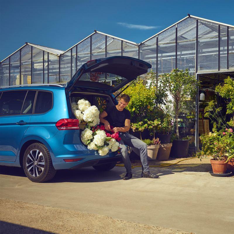 Mann sitzt in geöffneter Kofferraumklappe seines VW Touran mit etlichen Blumen neben ihm, im Hintergrund ein Gewächshaus