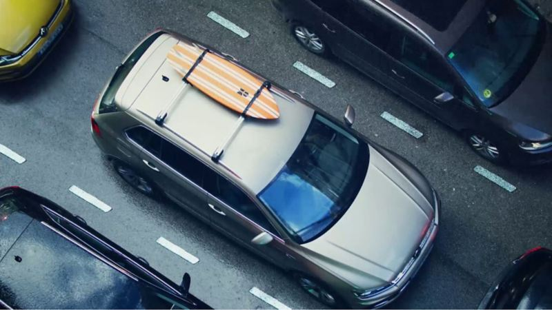 From a bird's-eye view a Volkswagen stands in a traffic jam, on its roof a surf board is fixed
