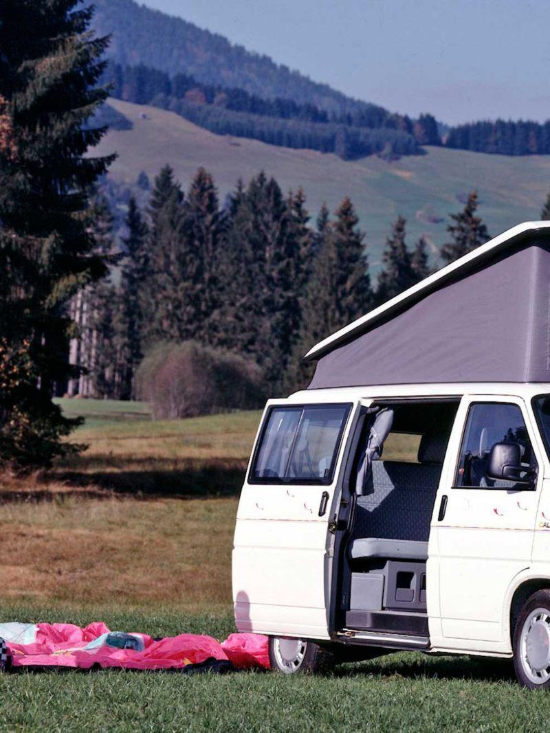 Um casal que faz parapente está parado junto à Transporter 4.