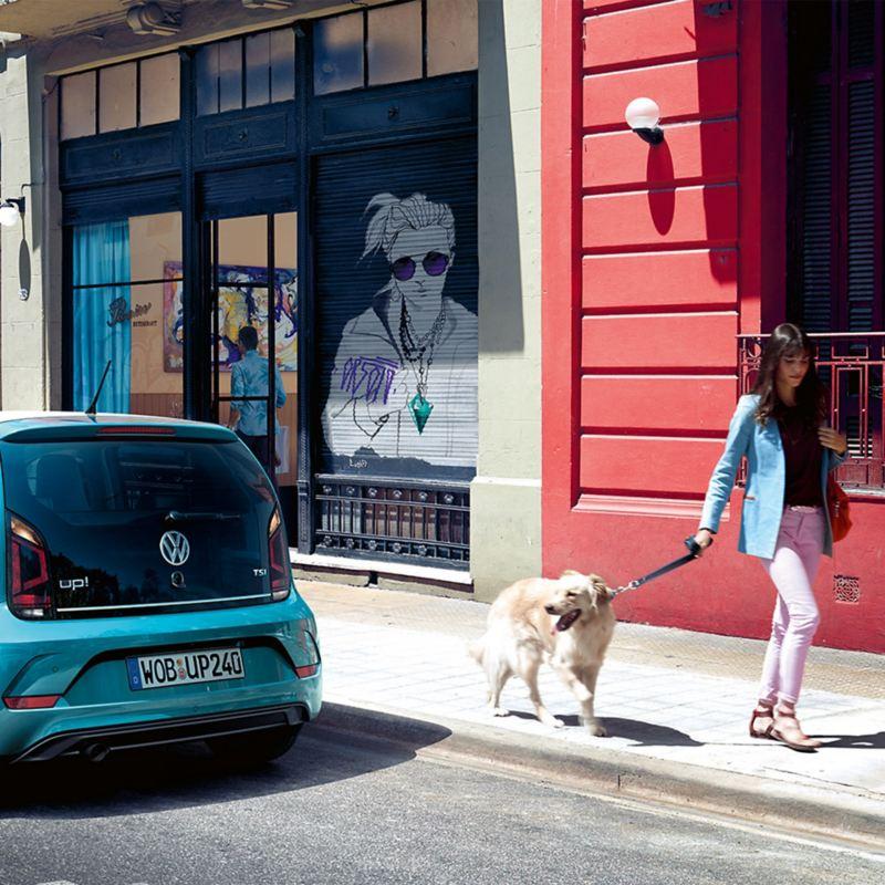 Frau geht mit ihrem Hund an ihrem Auto vorbei - Neuwagen beim Händler