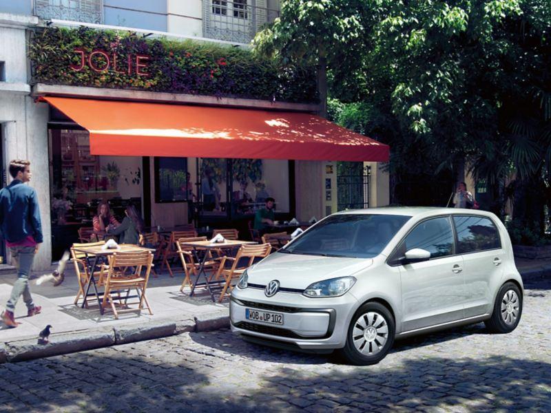 VW up! parkt auf Kopfsteinpflaster vor einem Straßencafé