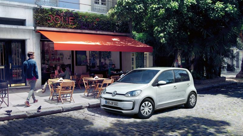 VW up! parks on cobblestones in front of a street café