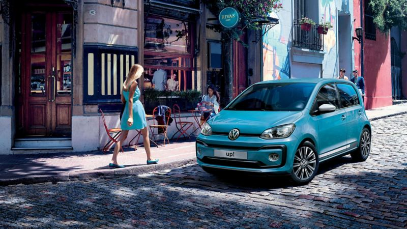 Volkswagen up! parcheggiata su una strada acciottolata davanti a un bar