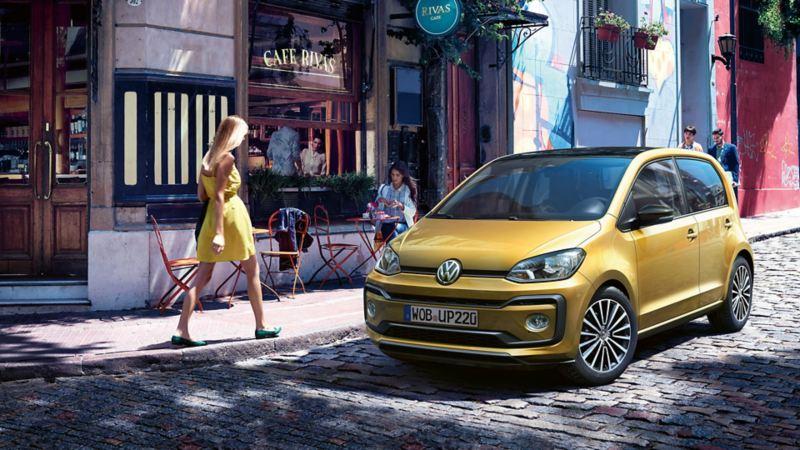 Volkswagen up! parkert i gate, kvinne går forbi
