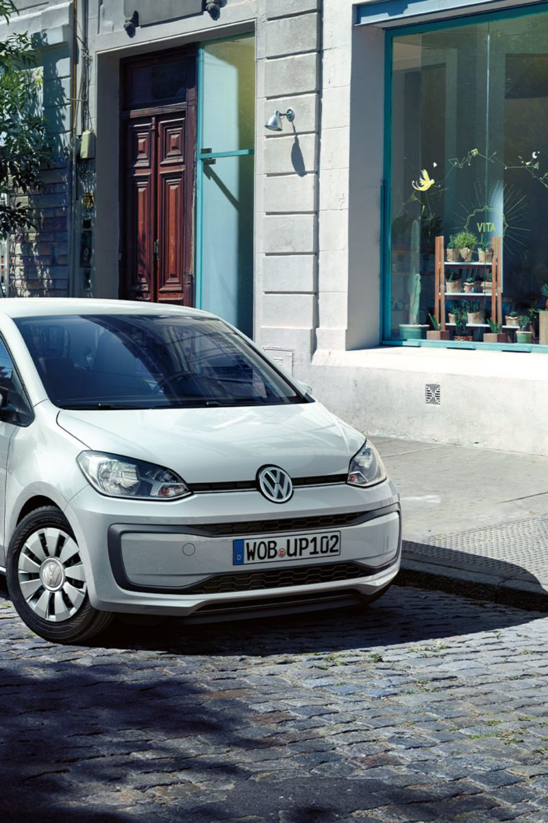 VW up! in front of little stores, diagonal view