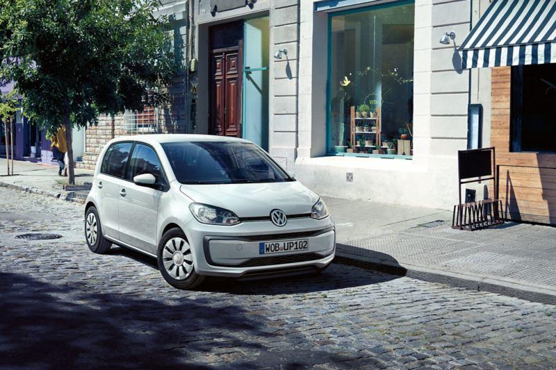 VW up! vor Geschäftszeile auf Pflasterstraße, Ansicht von schräg vorne