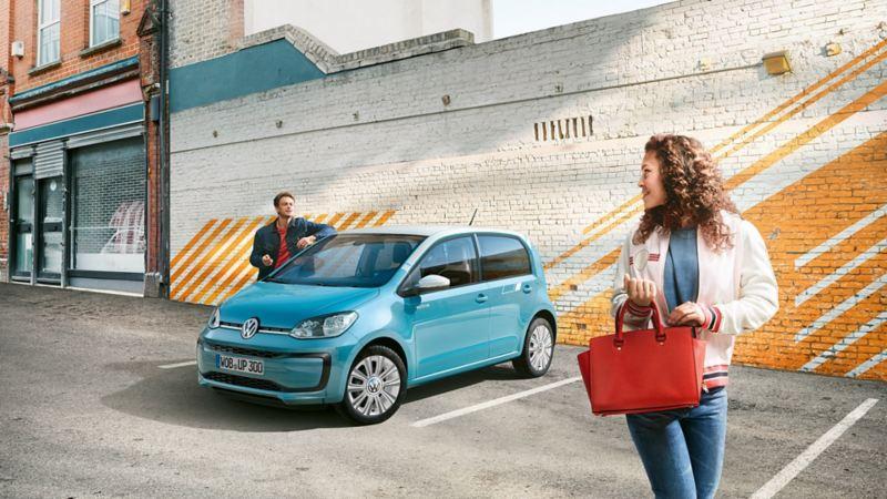 Homem junto ao VW spice up! em frente a uma parede com padrões, mulher em primeiro plano vira-se