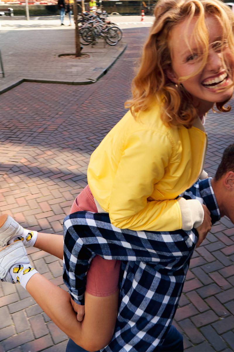 Mann trägt Freundin, up! IQ.DRIVE parkt im Hintergrund