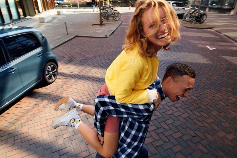 Un homme porte sa copine, une up! IQ.DRIVE est garée à l'arrière-plan.
