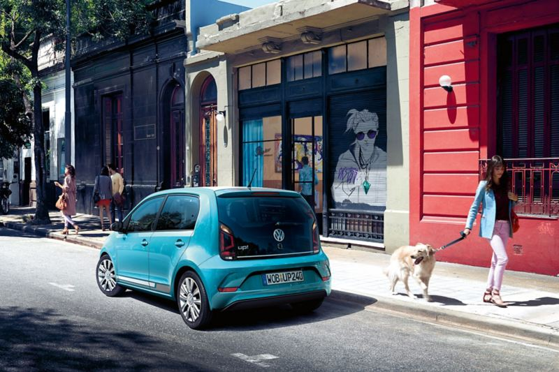 VW up! parks at the roadside in a trendy neighbourhood, woman with Golden Retriever goes for a walk, dog turns his head to the car