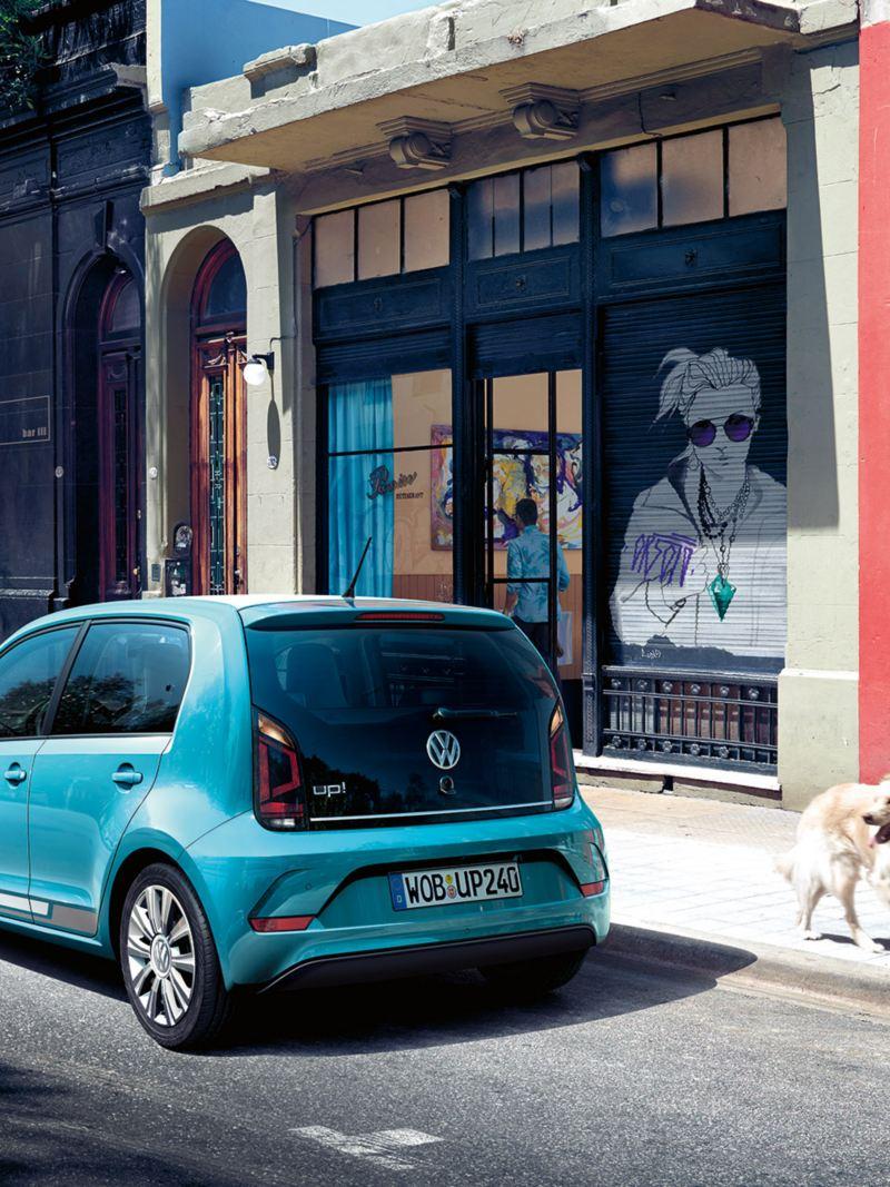 VW up! parkuje przy krawężniku, kobieta z golden retriverem spaceruje, pies ogląda się na samochód