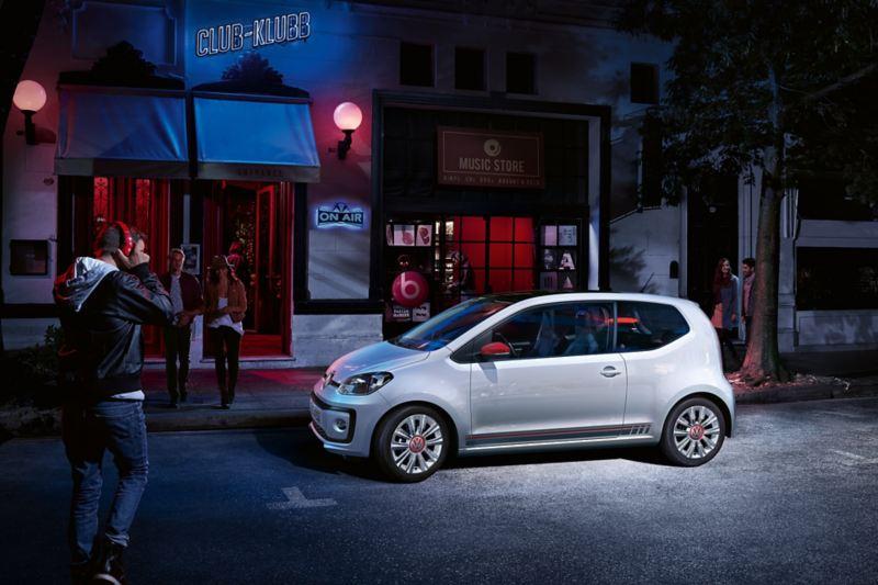 VW up! beats vor einem Klub auf Strasse in der Nacht
