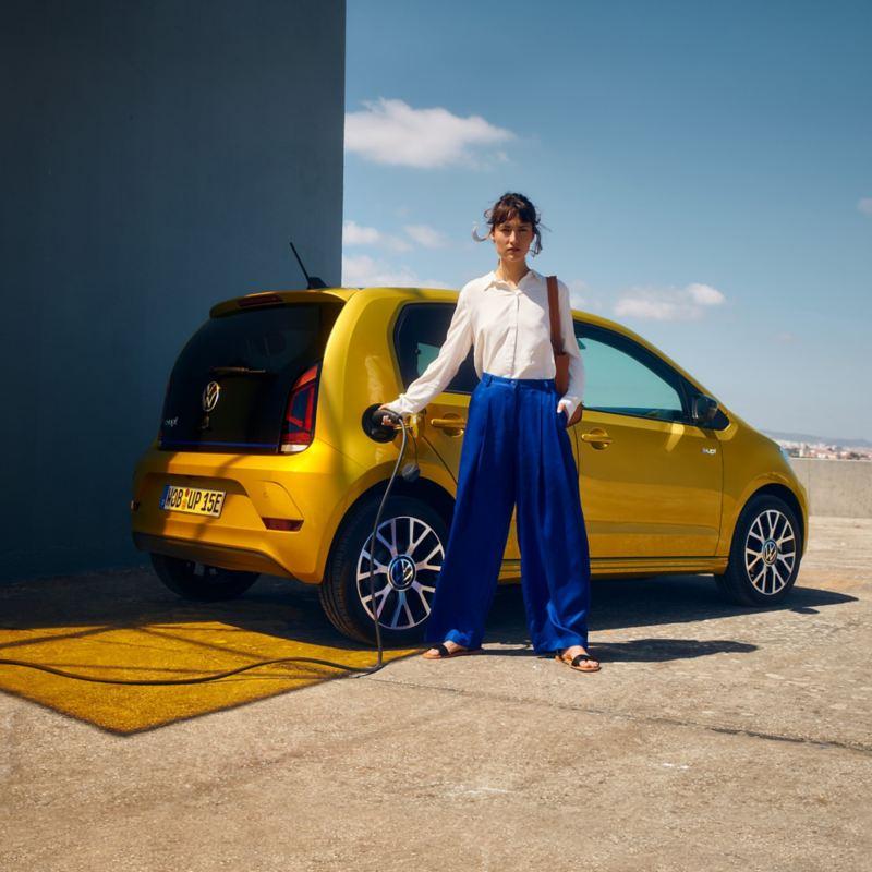 Frau lädt den VW e-up! an einer Wallbox auf