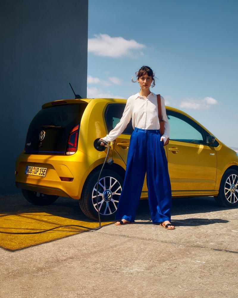 Frau steht vor VW e-up!, der gerade geladen wird.
