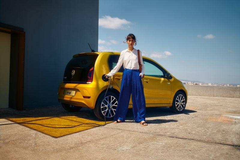 Donna inserisce Cavo di ricarica in Volkswagen e-up! auto elettrica