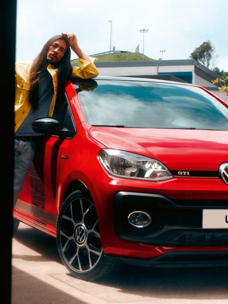Uomo appoggiato a Volkswagen up! GTI rossa