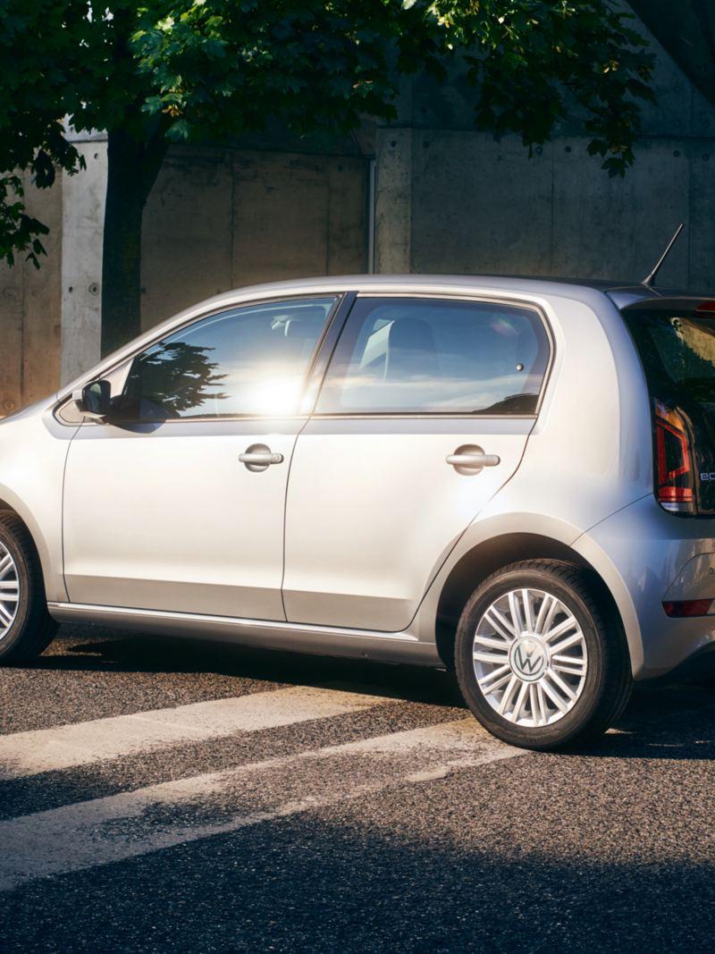 Il Sole si riflette sui finestrini di Volkswagen eco up! vicino ad una ragazza