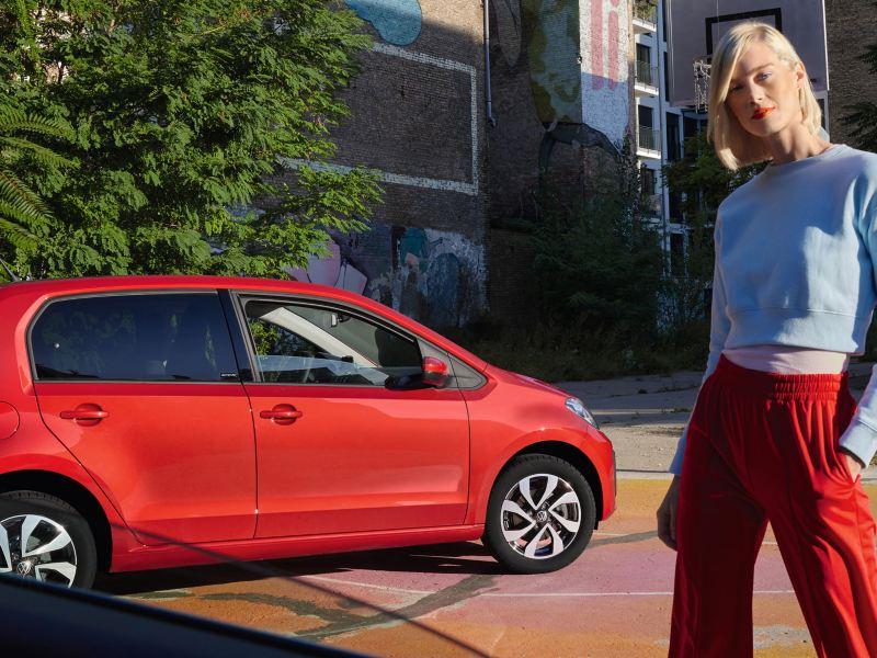 VW up! ACTIVE rouge devant des arbres verts dans une ville. Vue de côté et des roues.
