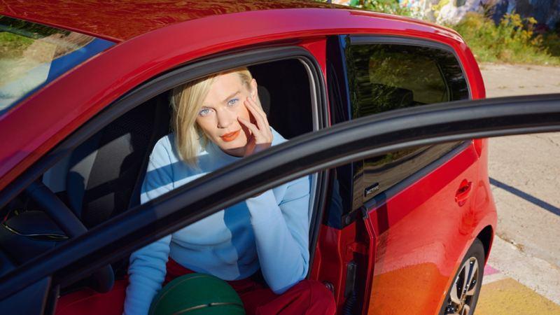 VW up! ACTIVE rouge avec porte ouverte sur le côté, de près. Femme en pull bleu sur le siège du conducteur.