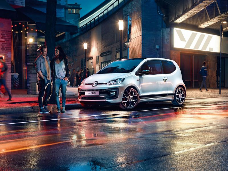 A white Volkswagen up! GTI parked on a well-lit city street at night.