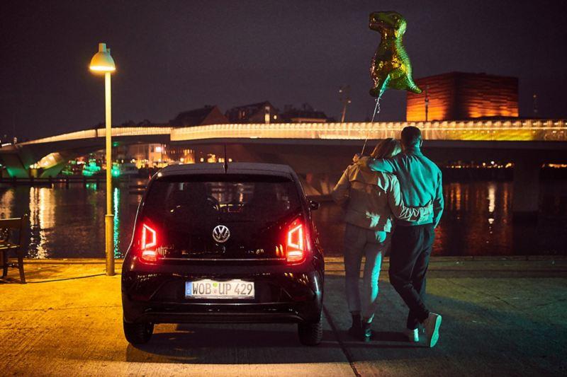 Paar steht neben ihrem Autos bei Nacht