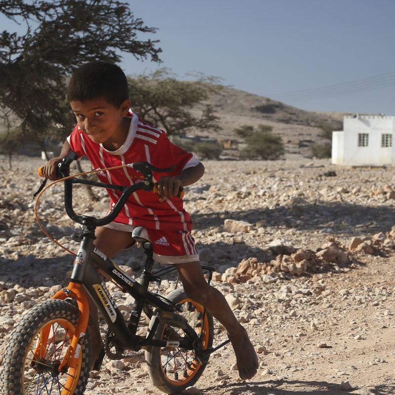 Liten kille på cykel i öknen