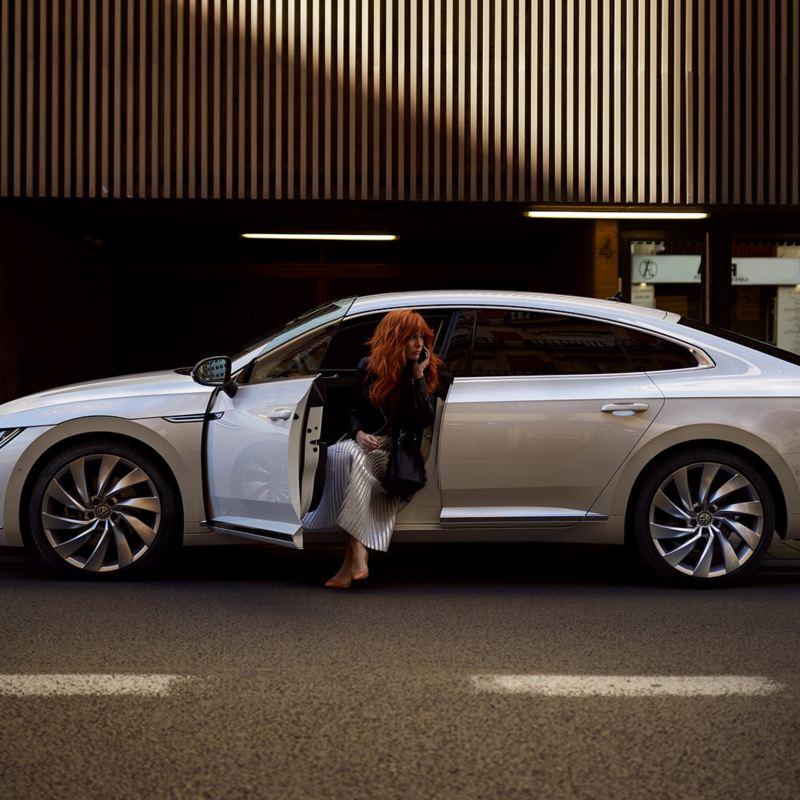 Una donna scende dalla sua auto Volkswagen Arteon