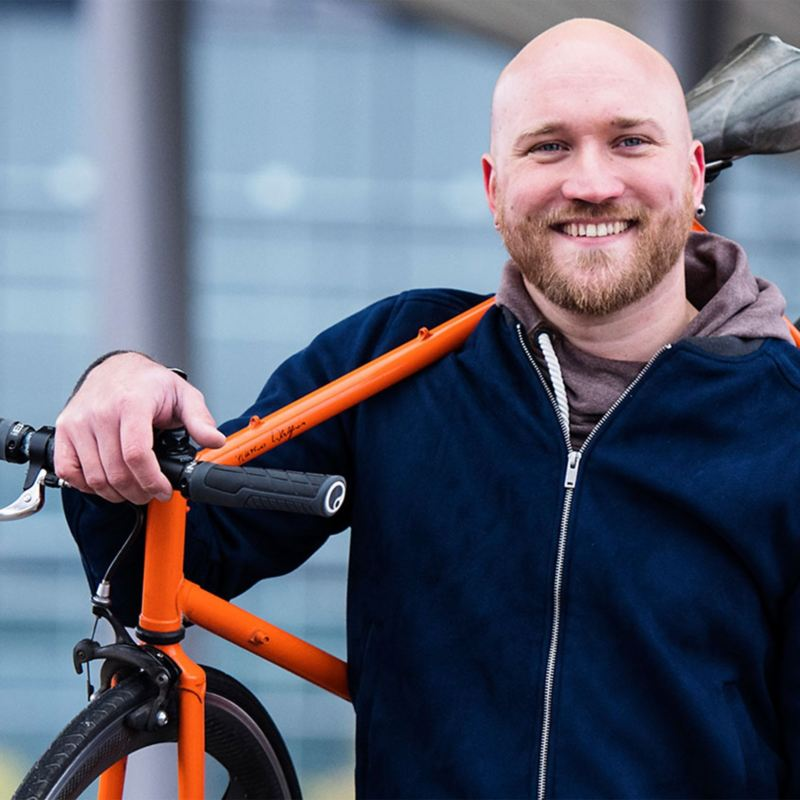 Man with a bicycle on his shoulder smiling into the camera