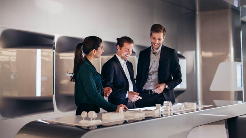 Drei Kollegen stehen vor einem Miniaturmodell